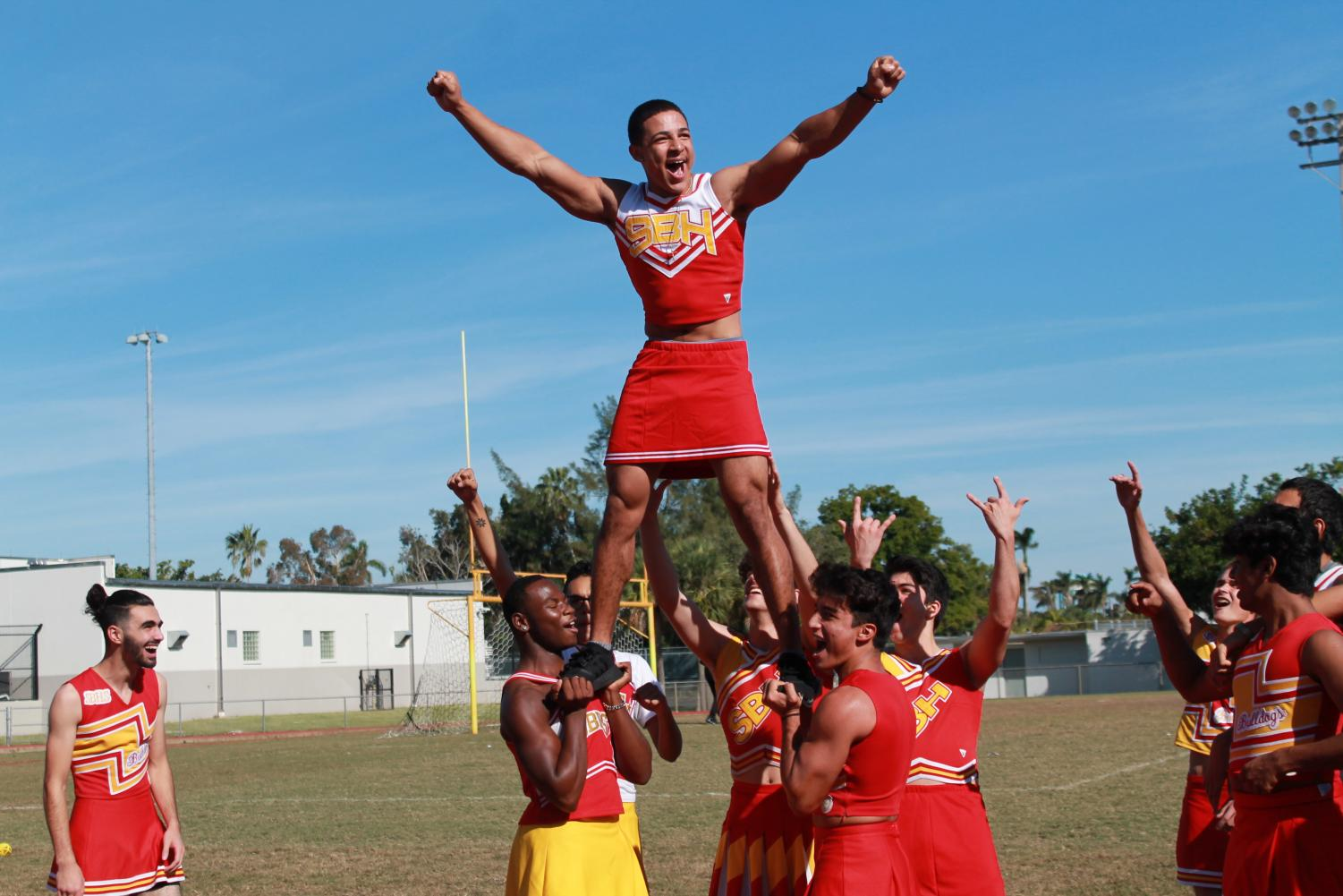 In this picture, Joel Pardilla,  is in a pyramid cheering.