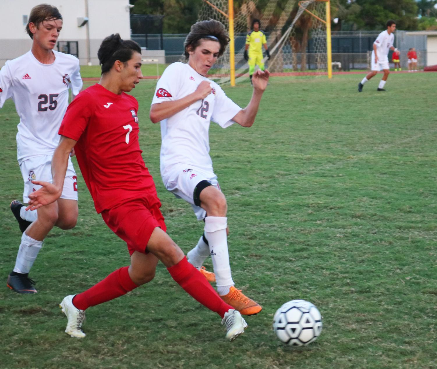 Jordan Ferreira, right wing, avoids a slide tackle from opposing team members.