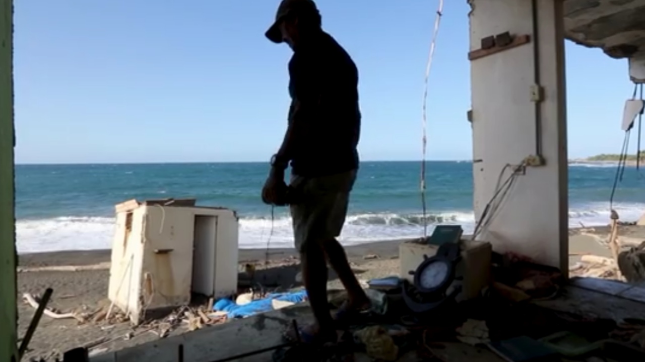 Alexander Gonzales picking through his torn up belongings after Hurricane Maria.