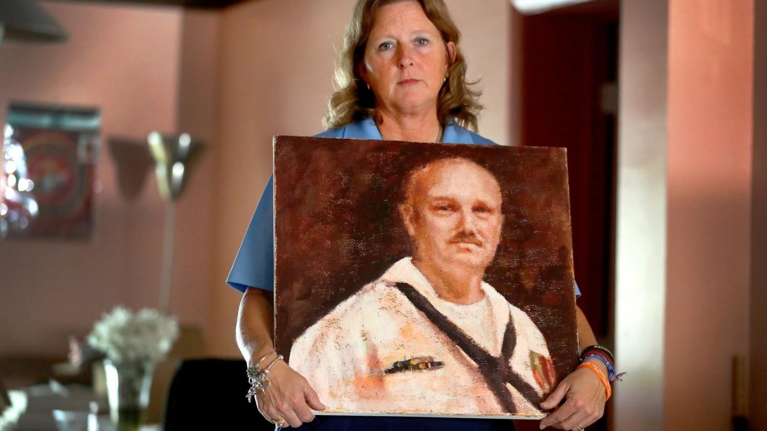 Debra Hixon holding up a painted portrait of her late husband.