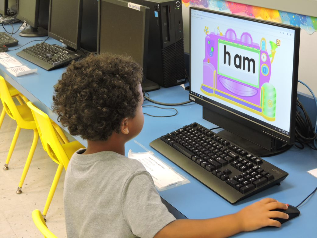 One of Ms.Batts Little Broward students, behind a monitor playing an educational Language Arts program.