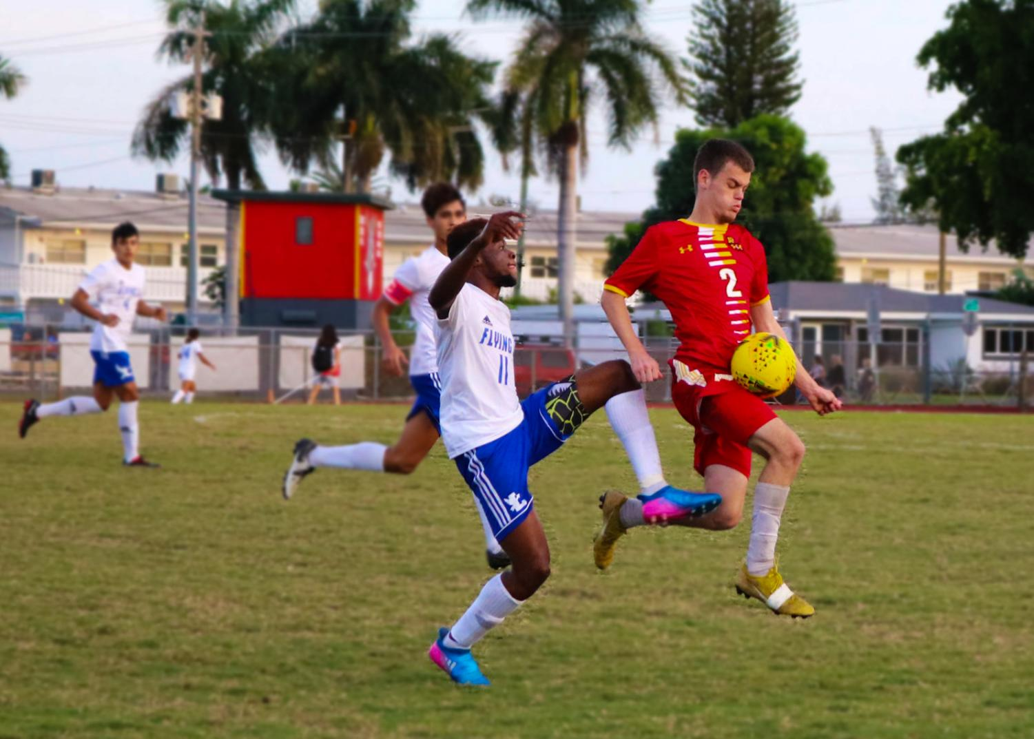 SBHS Bulldog Matthew Randall blocks the ball from an L player, in the first game of their season. SBHS boy's soccer team lost 1-0 against Fort Lauderdale High School.