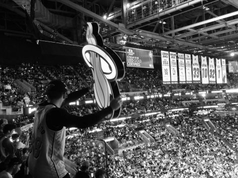 Miami Heat Hoop Troop waves around huge Heat logo to try and get people on they