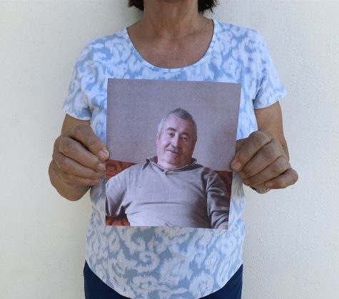 Rafila Bartos holds up picture of husband John Bartos, who is stuck in Romania during the corona virus outbreak.