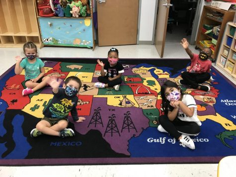 The preschoolers at the Little Broward Learning Lab sit and wave on the carpet, socially distant and with their batman, tie-dye, and floral patterned masks on.