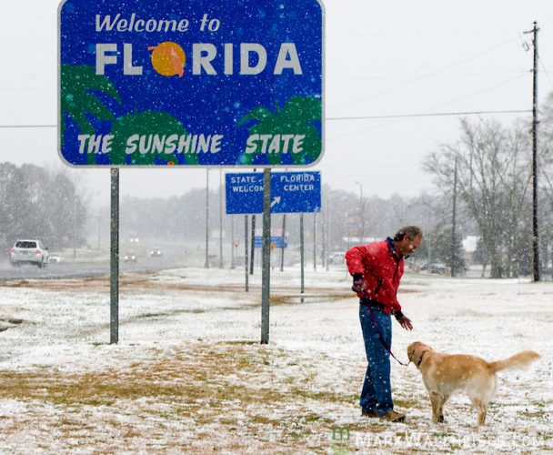 The welcoming sign of Florida surrounded by snow.