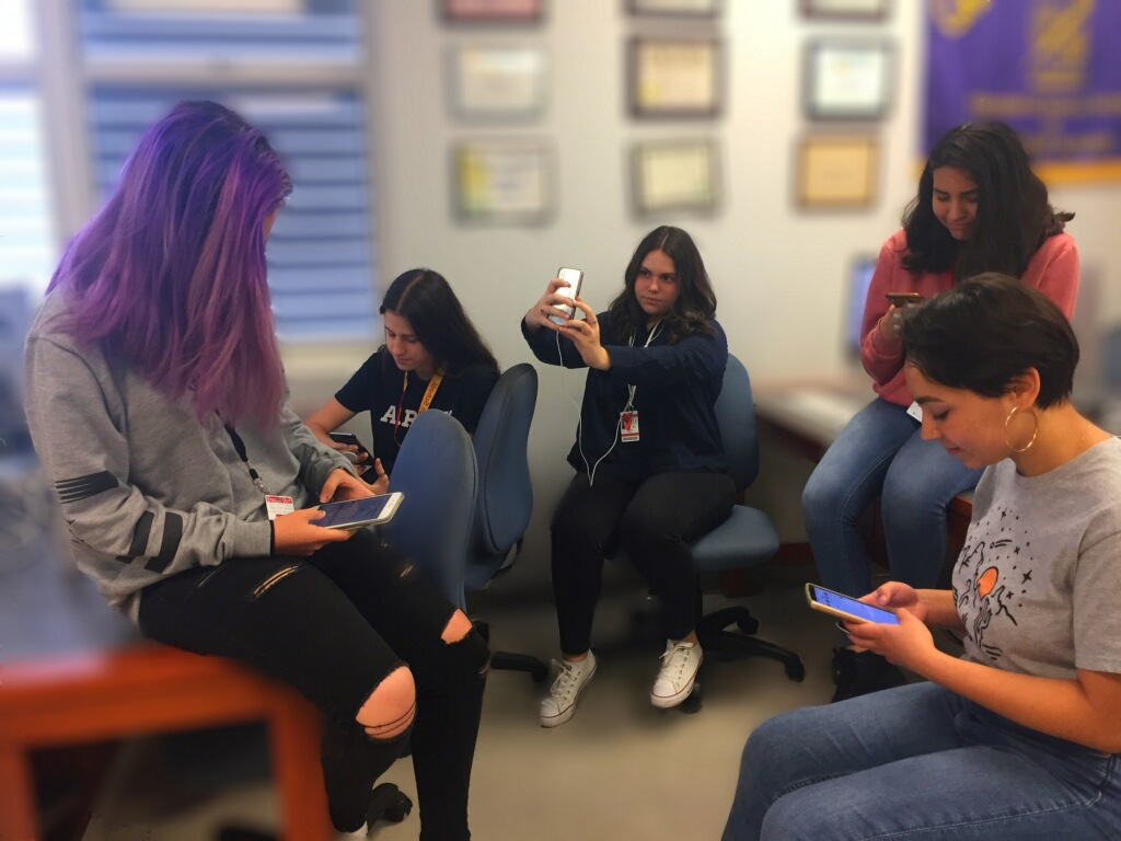 Teens on their phones, unaware of the fact that Mark Zuckerberg is selling the information they put up.