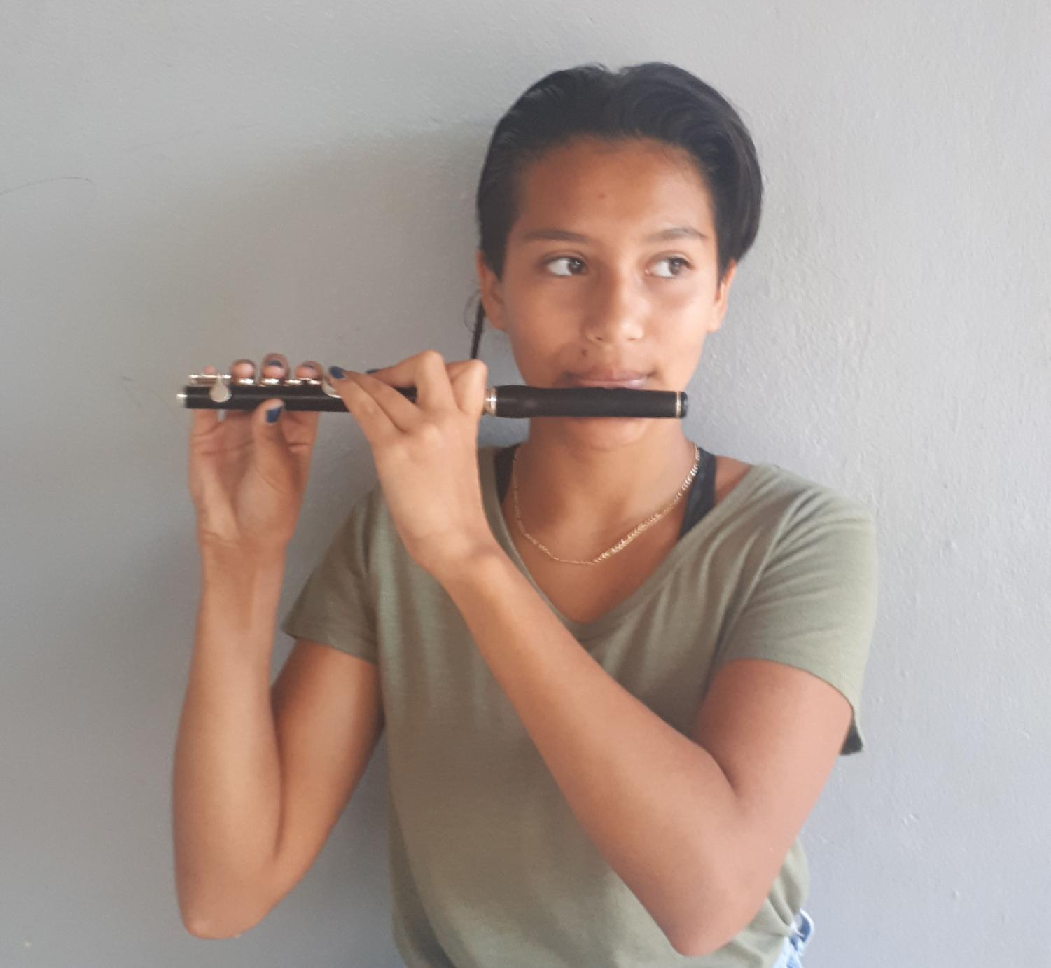 Emma shows off her piccolo skills to the camera in front of the band room.