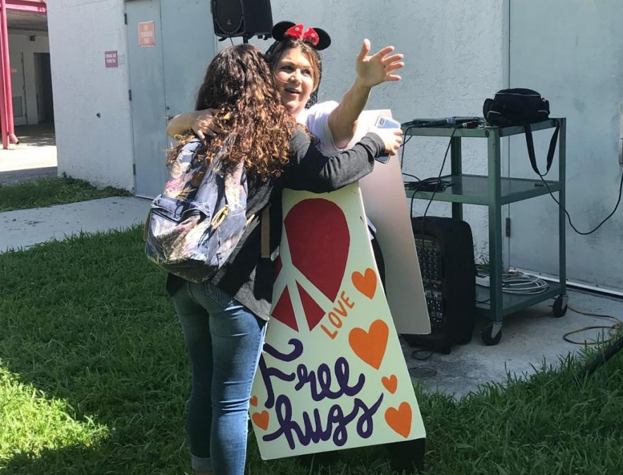 Ms. Adriana spreads peace and love as she offers free hugs to students . Student Nicole Rios gives in to the love .