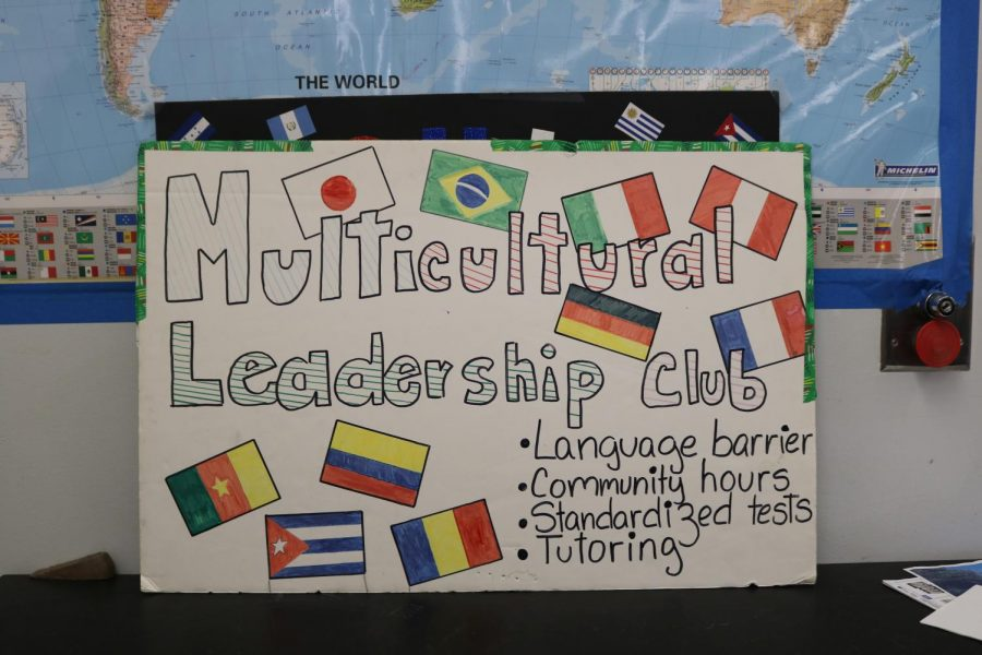 A sign hangs on Mr.Rodriguezs board encouraging people to join multicultural club for its benefits. He wants people of different lorigins to be able to help each other in tutoring and English skills.