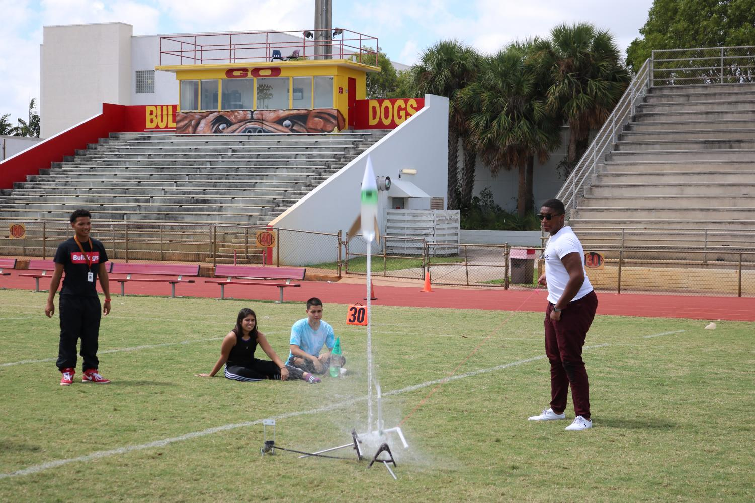 A rocket built by a student in Mr. Herrera's science class blasts off at the football field.