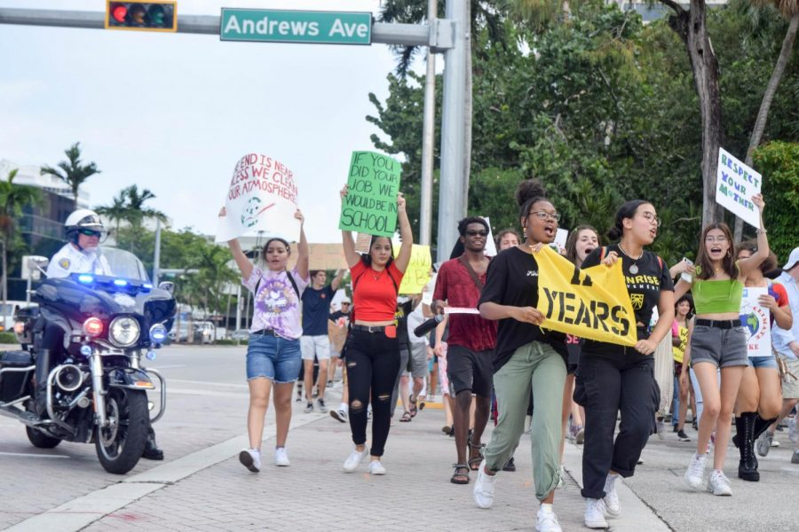 South Broward High School seniors Victoria Mejia and Francian Sonique march with an 11 years sign, at the Global Youth Climate Strike in Fort Lauderdale on September 20, 2019. The 11 years sign represents how many years society has left until Climate Change is irreversible. Many protesters used signs like these ones to express their opinions and beliefs at the strike.