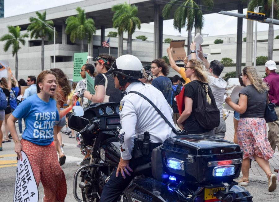 Nicole Buckley, a senior at Cypress Bay High School speaks to a police officer at the Global Youth Climate Strike in Fort Lauderdale on September 20, 2019. The protest was threatened to be shut down if the participants did not obey the traffic laws, Buckle, who helped organize the event made sure that did not happen.