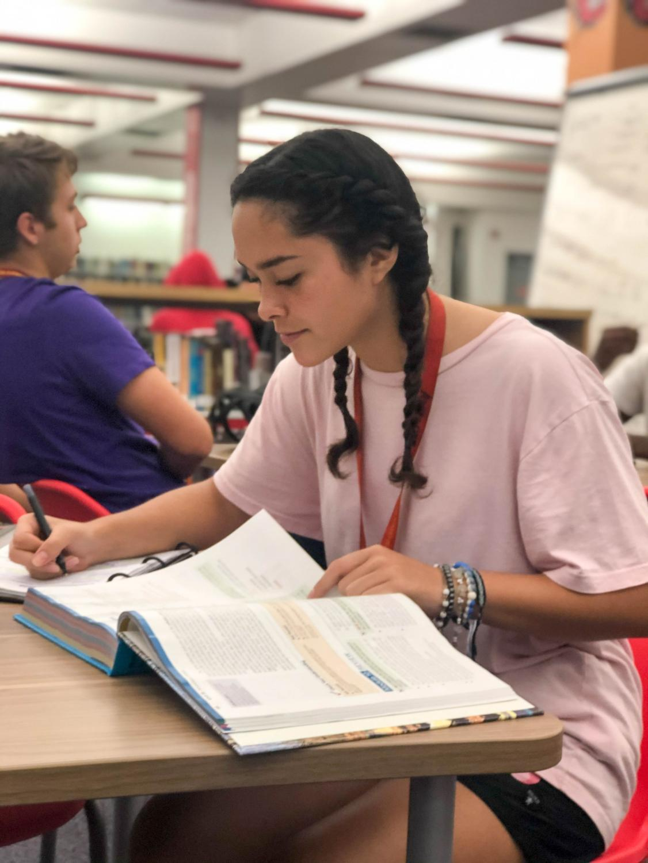 Senior Almendra Gutierez reading her textbook in the South Broward High School  library.