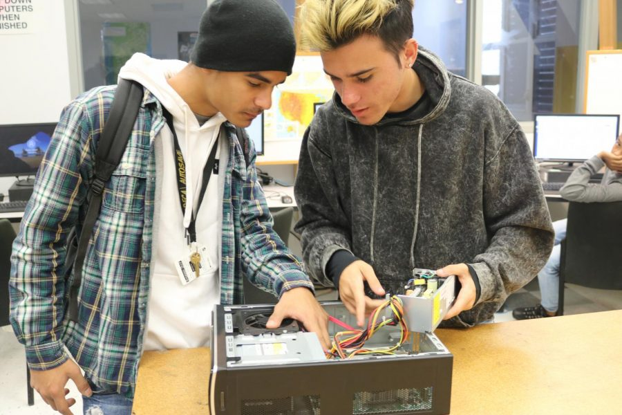Seniors Javier Gomez and Keiner Rangel work on a computer case in Ms.Kelly's 6th period Cyber Security class on November 18, 2019. The Cyber Security class is one of many classes here at South Broward that are being funded by the ICan grant.
