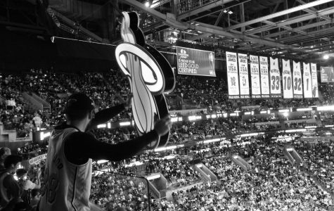 Miami Heat Hoop Troop waves around huge Heat logo to try and get people on they're feet. The Hoop troop is responsible for the entertainment of the people when the players aren't on the court.