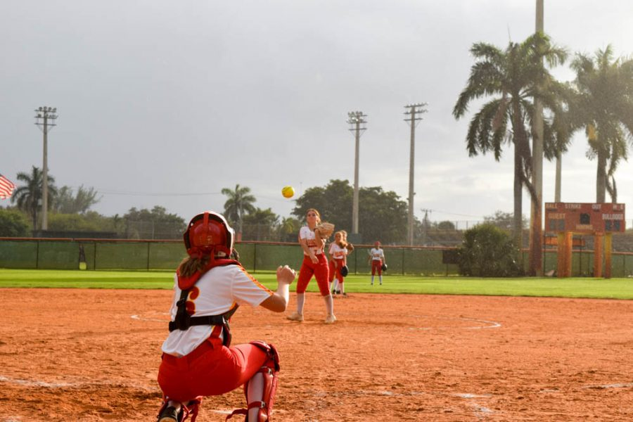 Pitcher Taylor Schirgio practices throwing with catcher Alexis Magliarisi at the South Broward High School girls softball game on February 20, 2020. Before the next inning starts all the team members practice catching and throwing to each other.