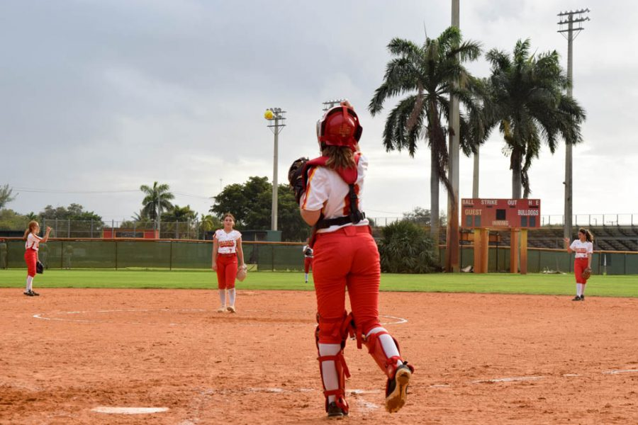Senior Alexis Magliarisi throws a softball back to pitcher, Taylor Schirgio, during the South Broward High School girls Softball Game on February 20, 2020. During the game, both Schirgio and Magliarisi used constant communication and teamwork to pass the ball back and forth when pitches were made.