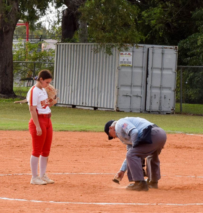 Pitcher Taylor Schirgio watches as the referee brushes dirt off of the pitchers mound. On February 20, 2020 South Broward High School took on Flanagan High Schools girls softball team.