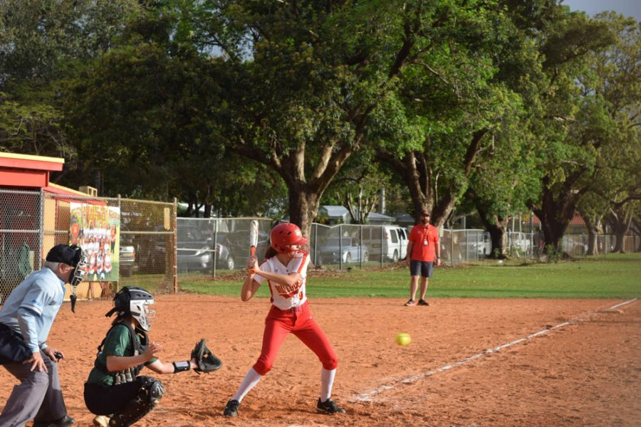 Anna Polanco swings at a fast ball approaching her at home base at their first game of the season on February 20, 2020. Coach Ryan March watches all the team members take their swing from the sidelines.