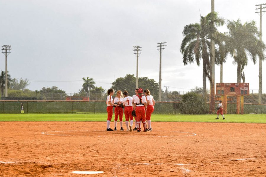 The South Broward girls Softball team meets at center field to discuss their next moves on February 20, 2020. The team played in rain and shine during their first game of the season against Flanagan High School.