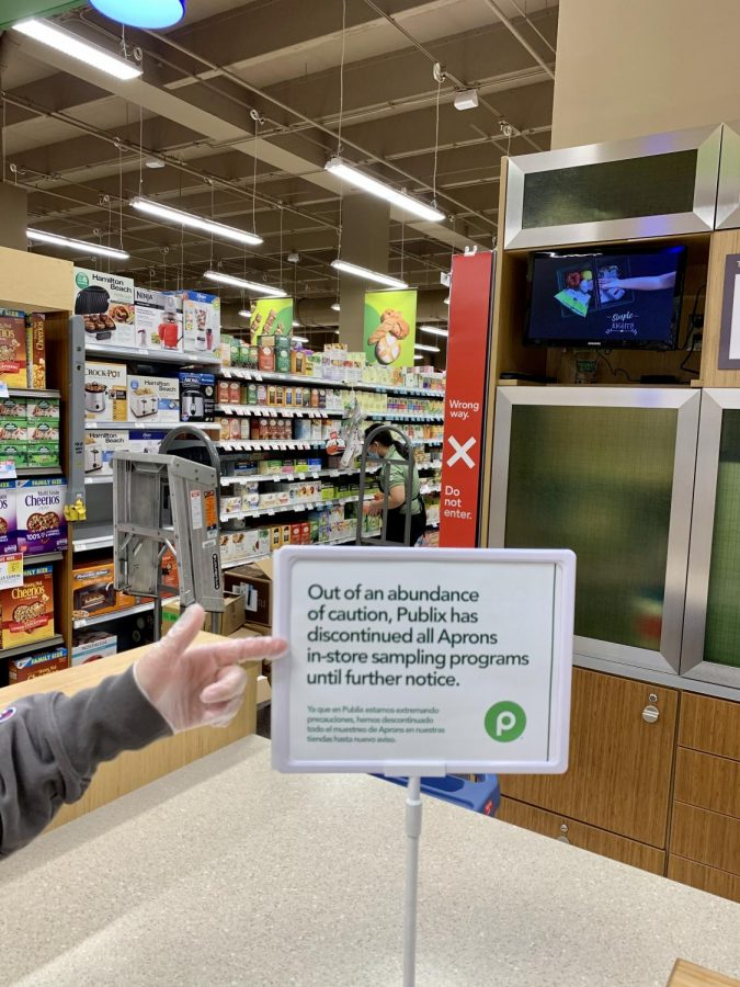 Customer points to a sign briefly explaining the inconvenience of in-store samples due to the COVID-19 virus. Photo by Clare Hutton-Perez