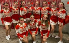 The South Broward cheer team posing and taking a picture after decorating the boys locker room for their game against Hallendale