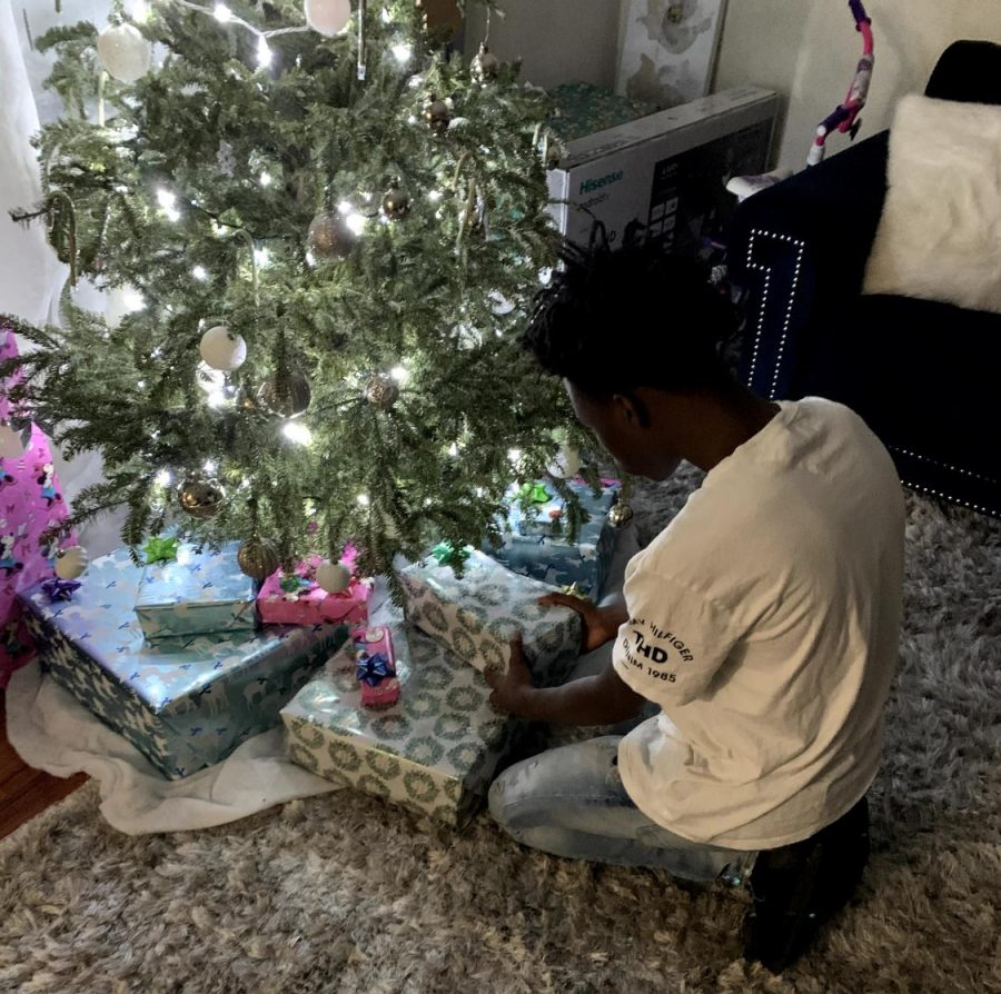 16 year-old, Calvin Lee is placing Christmas gifts under his tree.