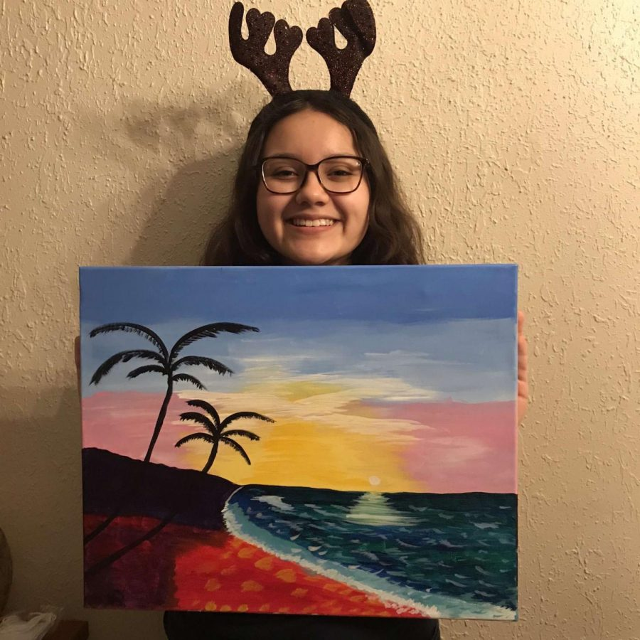 Selena Salmeron, 17, shows off a painting she made of the beach. The painting represents how beautiful the ocean can make a scene appear.