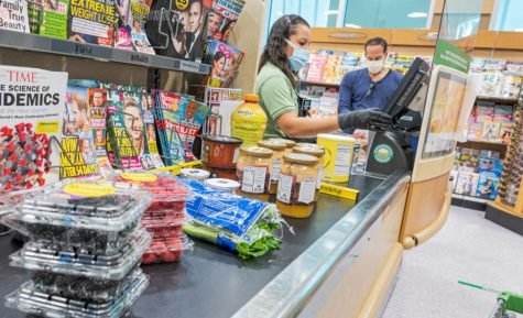 Publix cashier and customer wearing face masks and gloves, for protection against the virus.