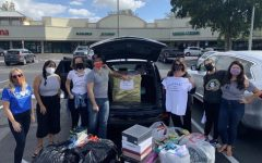 This photo was taken by Ms.Hixon as the volunteer's show the donations that were given at the clothing drive for the Women In Distress Thrift Store.