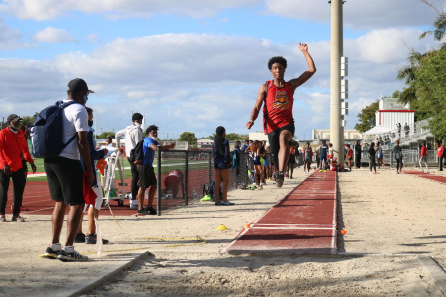 SBHS Senior Cameron Jones takes a leaping dive into the long jump pit during the track meet at Carndinal Gibbons on March 9th. Jones took first place in the long jump out of 23 jumpers after jumping 25.3 meters.