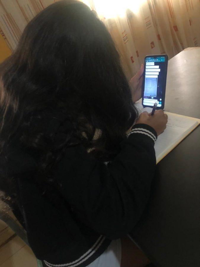 Geslie Range doing her  work from online schooling.