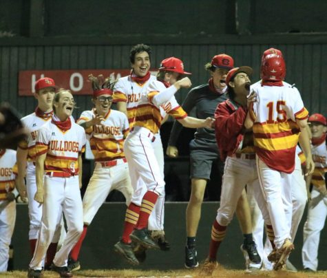 Junior Lucas Scimeca (15) jumps for joy as hes mobbed by teammates and scores the game-winning run against Cooper City on February 22, 2021.