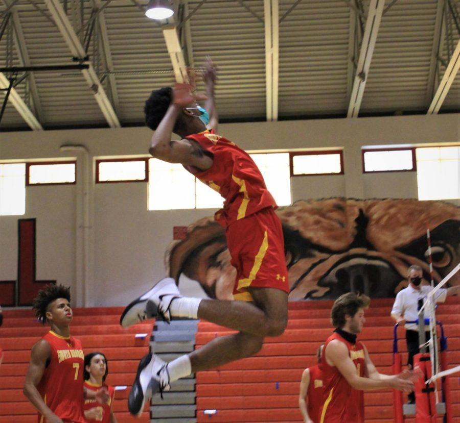Senior, Oshane Farquharson (10), leaps high into the air and prepares to hit the oncoming ball.