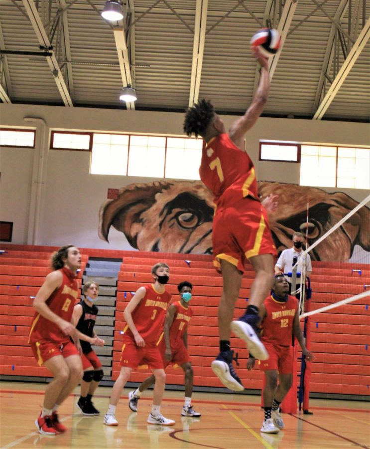 Junior, Cameron Thorne (7) hops into the air and hits the ball back over the net.