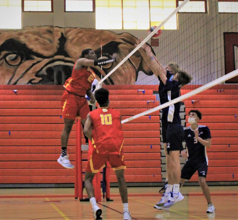 Jonathan Hardaway (12) hits the ball over the net. Two players on the opposing team, Chaminade High School, attempt to stop the ball.